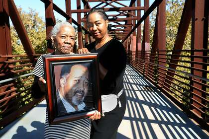Catherine Lawson (left) carries a picture of her husband, Jerry Lawson, with their daughter Karen Lawson in San Jose. Jerry Lawson, a pioneer of Silicon Valley, died in 2011.