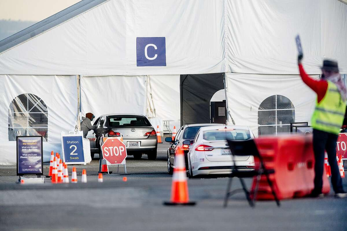 Cars drive through a coronavirus testing site at Pier 30 in San Francisco. The city has curbed the coronavirus well, but some fear the long-term economic fallout.
