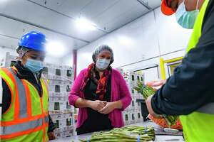 Zaira Escalera, left, and CEO Judy Clark watch as Lupe Torres, right, inspects asparagus at Fresh Texas.