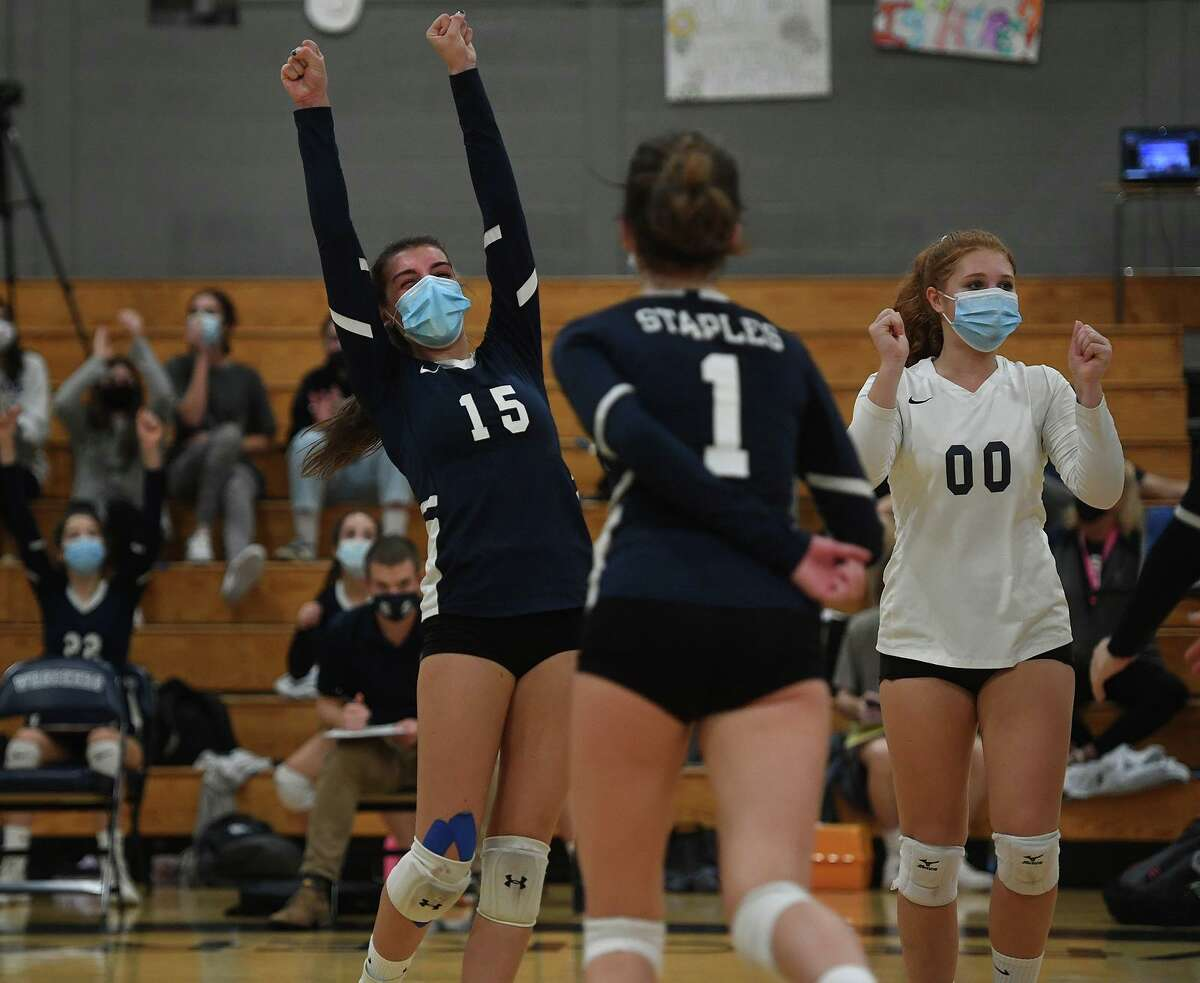 From left; Staples teammates including Kaytlyn Carnahan, left, and Nicole D'Erario, right, celebrate their victory over Ridgefield in the FCIAC Central Volleyball championship match at Staples High School in Westport, Conn. on Tuesday, November 10, 2020.