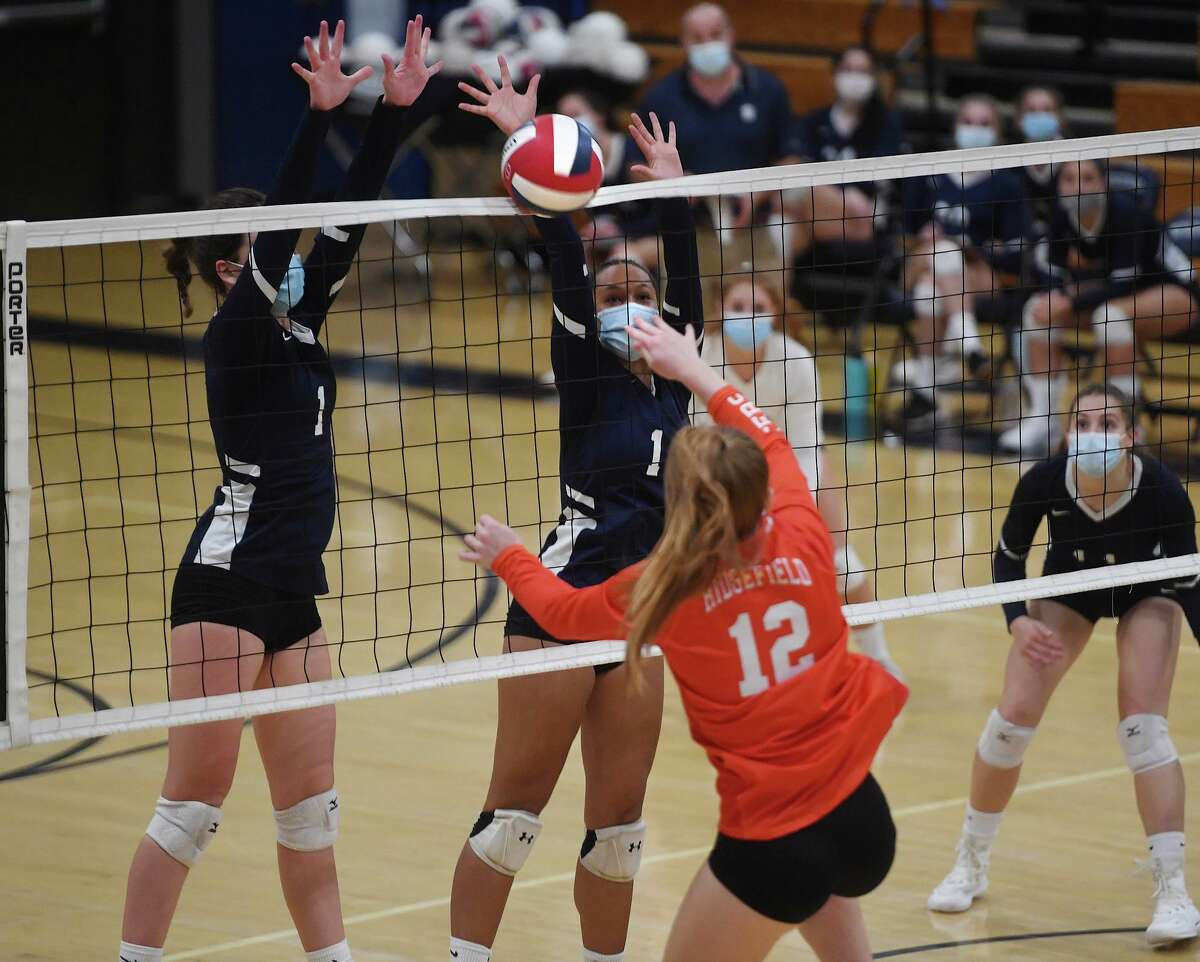 Staples teammates including Linnea Jagenberg, right, rise up to block a spike by Ridgefield's Ellie Brady during the Wreckers' 3-0 victory over Ridgefield in the FCIAC Central Volleyball championship match at Staples High School in Westport, Conn. on Tuesday, November 10, 2020.