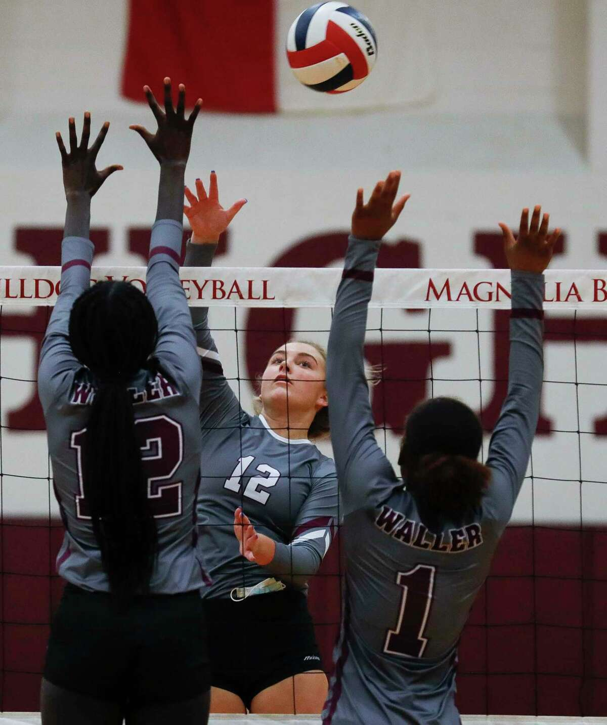 Magnolia outside hitter Sydney Gentry (12) gets a shot over Waller middle blocker Nyanath Ruot (12) and right side hitter Essence Williams (1) during the first set of a District 19-5A high school volleyball match at Magnolia High School, Tuesday, Nov. 10, 2020, in Magnolia.