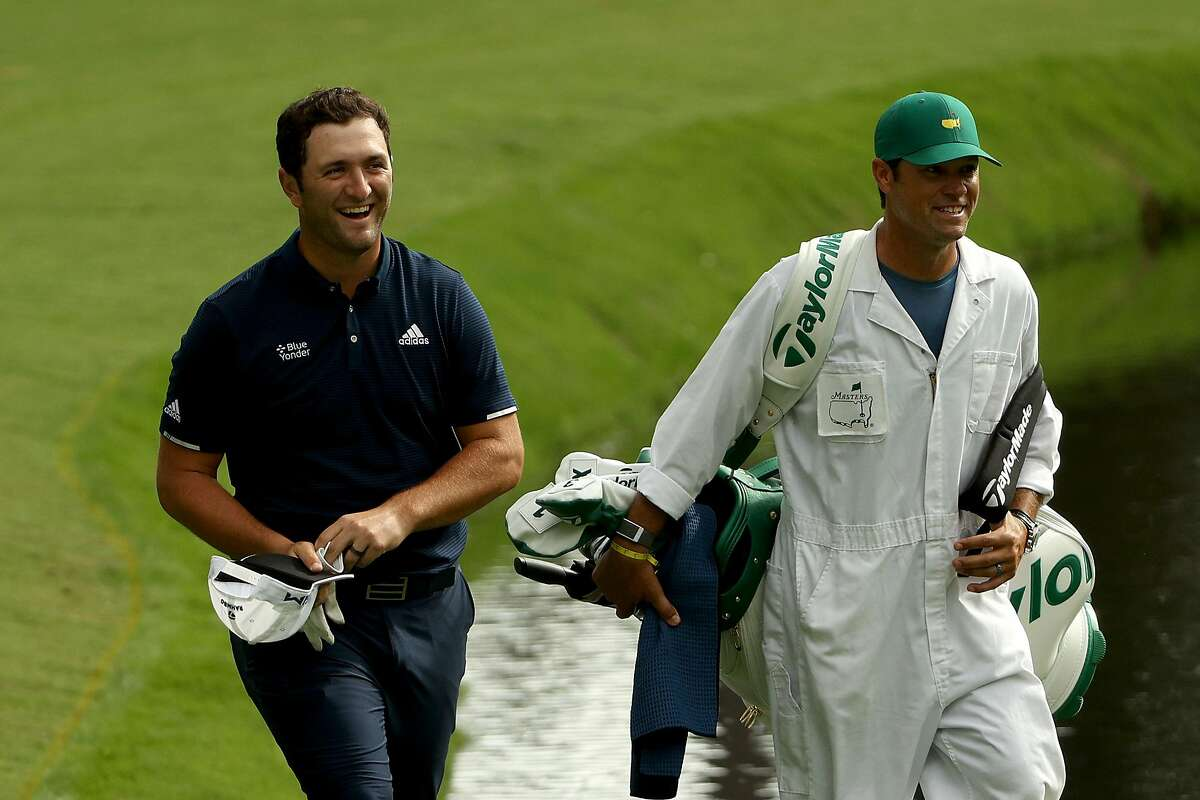 Jon Rahm laughs with caddie Adam Hayes after a remarkable hole in one on 16 during practice Tuesday.