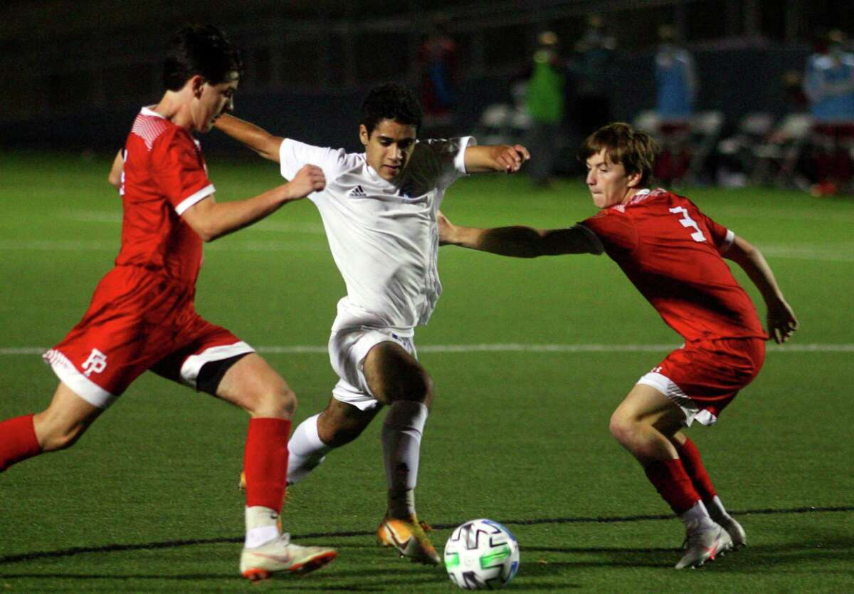Fairfield Ludlowe's Malik Thomas, center, drives the ball to the goal as Fairfield Prep players Jack Hickey , left, and Harrison Steffens converge to block during FCIAC East boys soccer championship action in Fairfield, Conn., on Tuesday Nov. 10, 2020.
