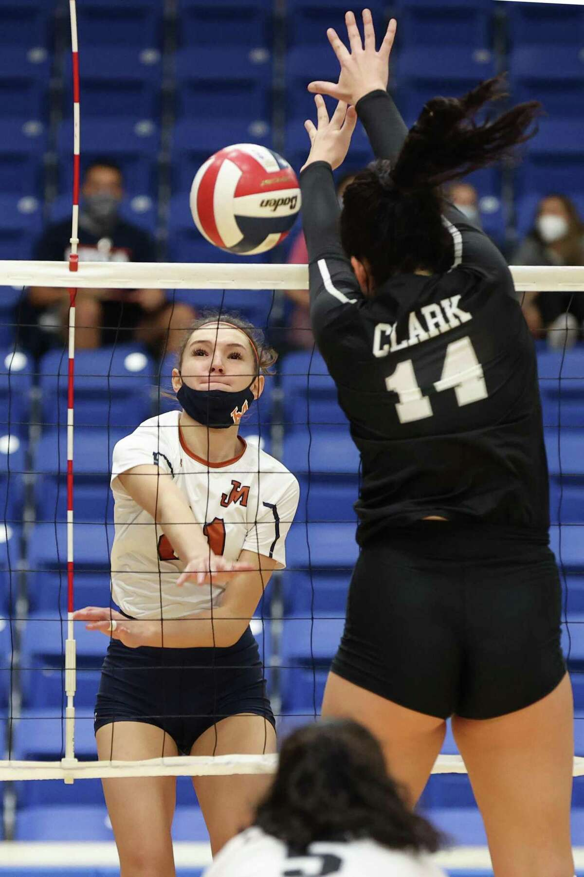 Madison's Mia Dorsey, left, hits the ball past Clark's Elise McGhee during their District 28-6A volleyball match at Northside Gym on Tuesday, Nov. 10, 2020. Clark won the match in four sets: 25-23, 25-21, 20-25, 25-22.