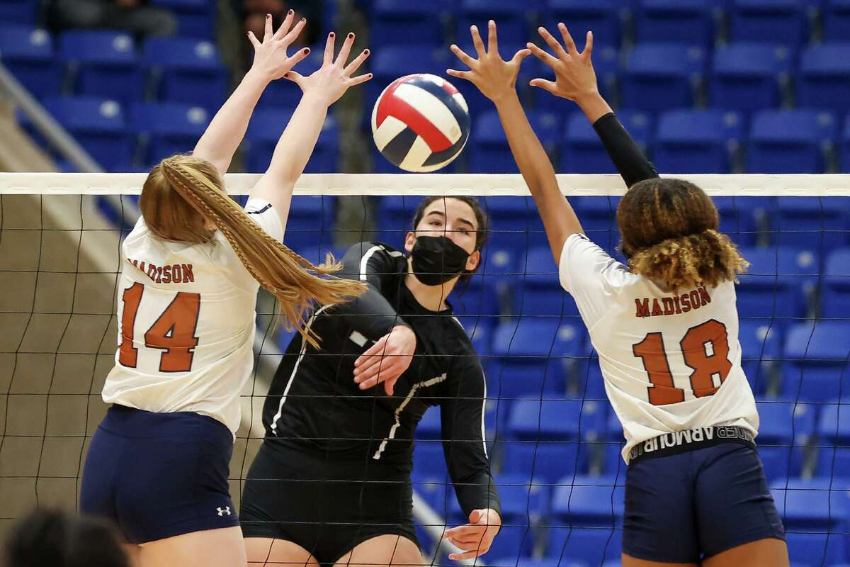 Clark's Elise McGhee, center, gets a kill shot past Madison's Shavonne Responkdek, left, and Dallasstar Johnson during their District 28-6A volleyball match at Northside Gym on Tuesday, Nov. 10, 2020. Clark won the match in four sets: 25-23, 25-21, 20-25, 25-22.