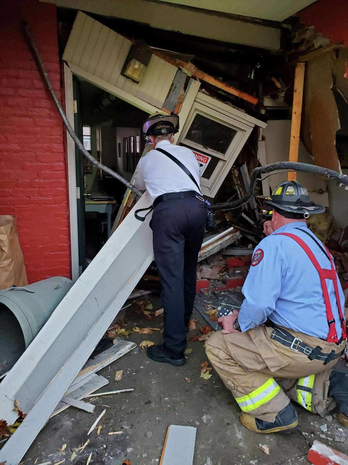 Troy firefighters examine the damage at the rear of the Kate Mullany National Historic Site at 350 Eighth St., Troy, N.Y. on Tuesday Nov. 10, 2020 after a vehicle crashed into the building.