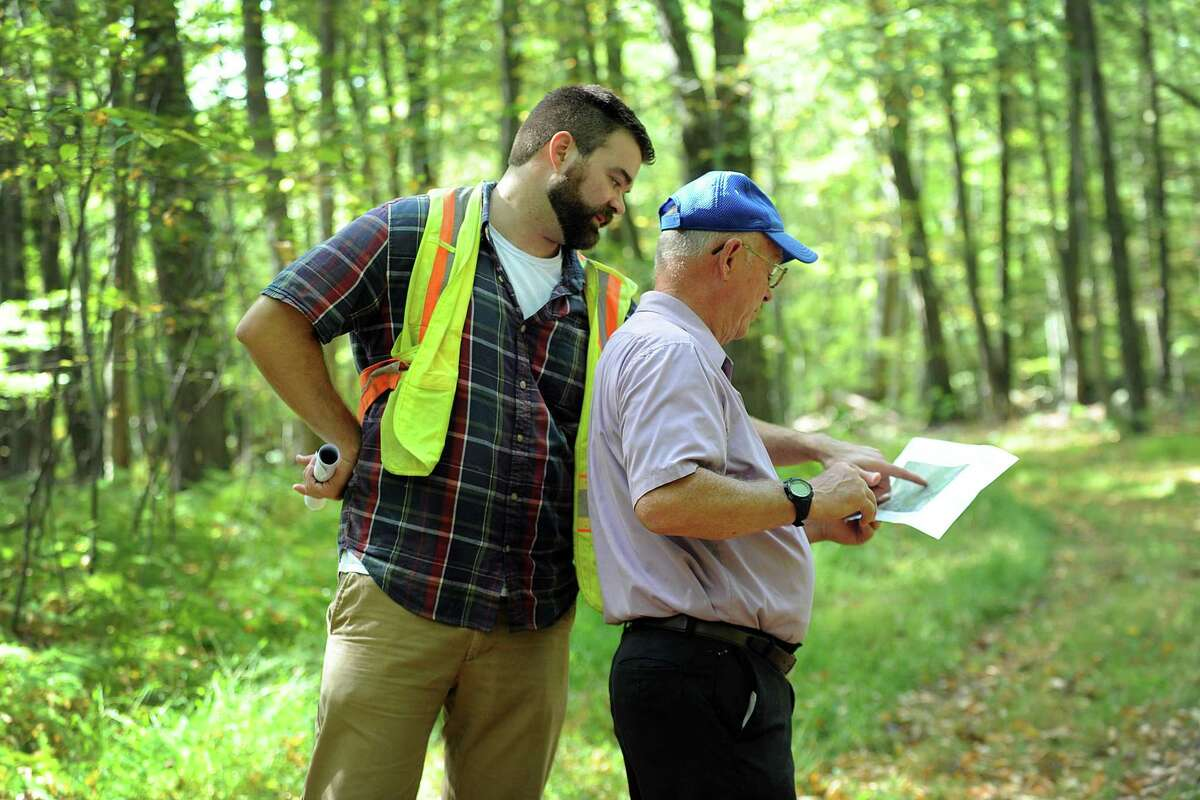 Paul Delmar, left, with Ameresco Candlewood Solar, and Frank Wargo, a town councilman, look at a map of the area where a solar panel array is proposed. The state Siting Council does a walking tour of the area where there is a proposal to build solar panels on Candlewood Mountain in New Milford, Tuesday, Sept. 26, 2017.