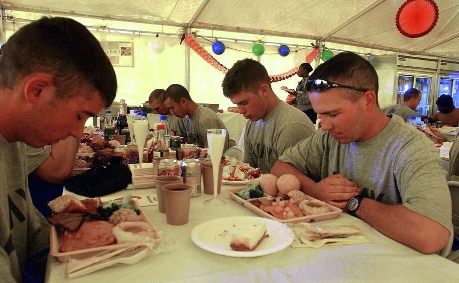 U.S. Army soldiers bow their heads prior to Thanksgiving dinner Nov. 28, 2002, at Bagram Airbase in Afghanistan. (Photo by Scott Nelson/Getty Images) / 2002 Getty Images