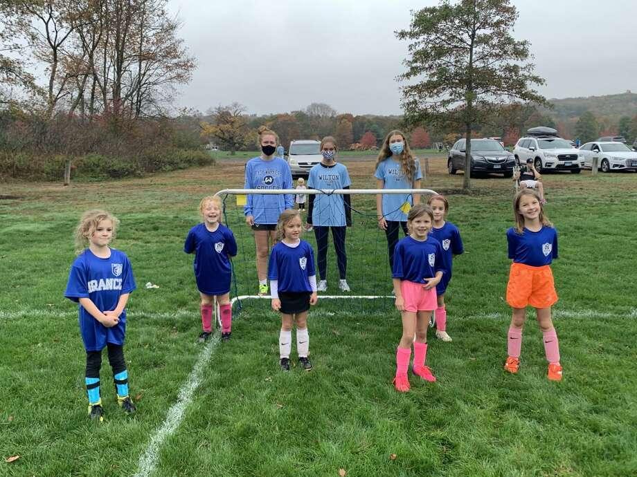 Members of the Wilton High School boys and girls soccer teams visited younger players in the Wilton Soccer Association last month. Photo: Contributed Photo / Wilton Soccer Association