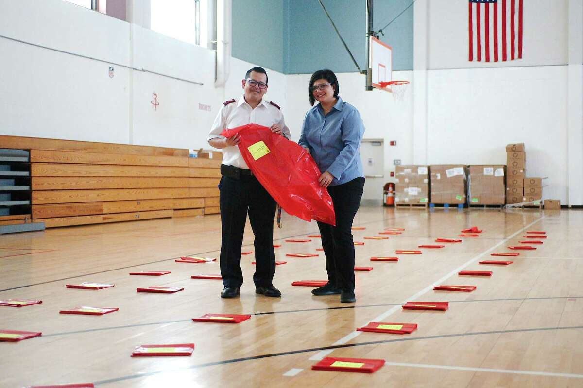 Salvation Army Lt. Luis Villanueva and his wife Marianne stand among rows of red bags that the organization's East Harris County chapter hopes to fill with toys for around 1,500 children and gifts for about 200 senior adults. The group is calling for donations and volunteers.