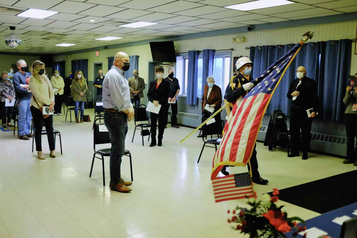 George DeLong, a member of the Son's of the American Legion Post 927, carries the American Flag to the front of the room during a ceremony at the Green Island American Legion on Wednesday, Nov. 11, 2020, in Green Island, N.Y. (Paul Buckowski/Times Union)