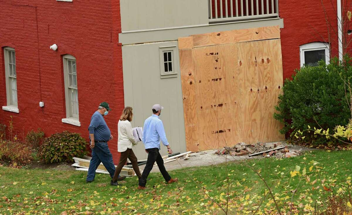 Paul Cole, executive director of the Kate Mullany National Historic Site, left, walks with renovation people to show the damage to the Kate Mullany National Historic Site house on Wednesday, Nov. 11, 2020 in Troy, N.Y. The house was badly damaged Tuesday afternoon when an SUV crashed through the rear of the building and rolled into the structure. (Lori Van Buren/Times Union)