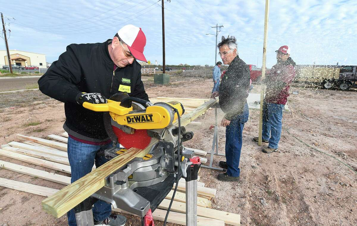 Briggs Equipment team members George Kawas, Derly Cuellar and Alex Campos cut a two by four for a frame, Saturday, Feb. 29, 2020, at the construction site for a Habitat for Humanity home near Hwy 359.