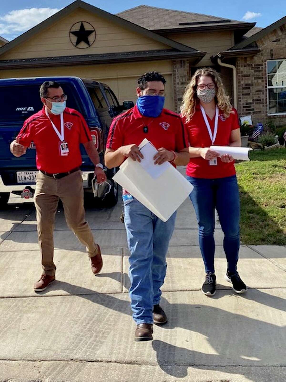 Southside ISD Superintendent Mr. Rolando Ramirez, custodian Mr. Paul Marquez, and technology specialist Ms. Wendy Luna distribute flyers.