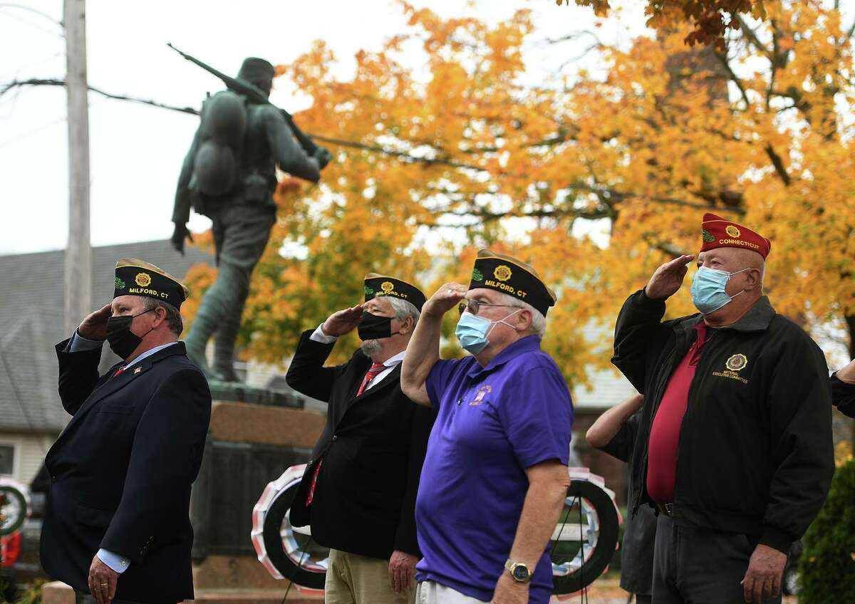 Milford veterans salute the flag for the playing of the National Anthem during the annual Veterans Day ceremony at the World War One monument outside City Hall in Milford, Conn. on Wednesday, November 11, 2020.