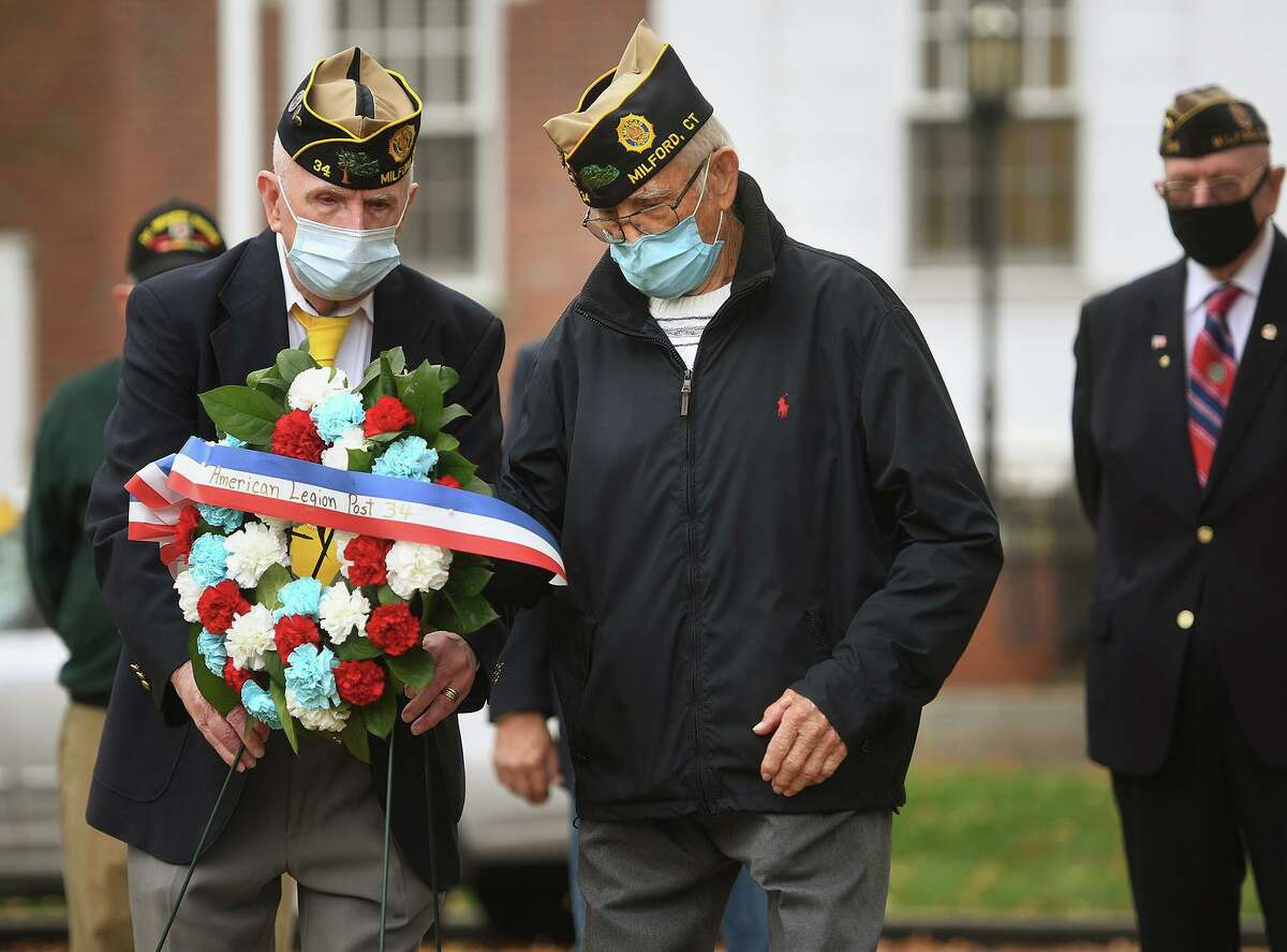 Korean War vet Bob Sherrick, left, and World War 2 vet Wayne Carson, both of Milford, place a wreath for American Legion Post 34 during the annual Veterans Day ceremony at the World War One monument outside City Hall in Milford, Conn. on Wednesday, November 11, 2020.