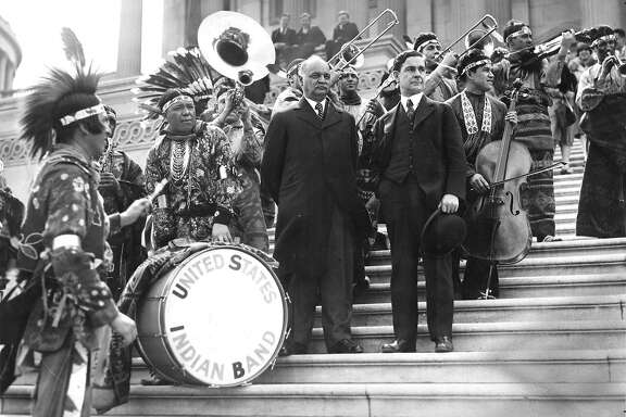 """FILE -- Vice President Charles Curtis, center, attends a performance by the United States Indian Band on the steps of the Capitol in Washington on May 11, 1929. Historians and Native Americans are revisiting the legacy of Curtis, whose Kaw Nation ancestry gives him a claim as the first """"person of color"""" to serve as vice president, though the term's current usage emerged decades later. (The New York Times)"""