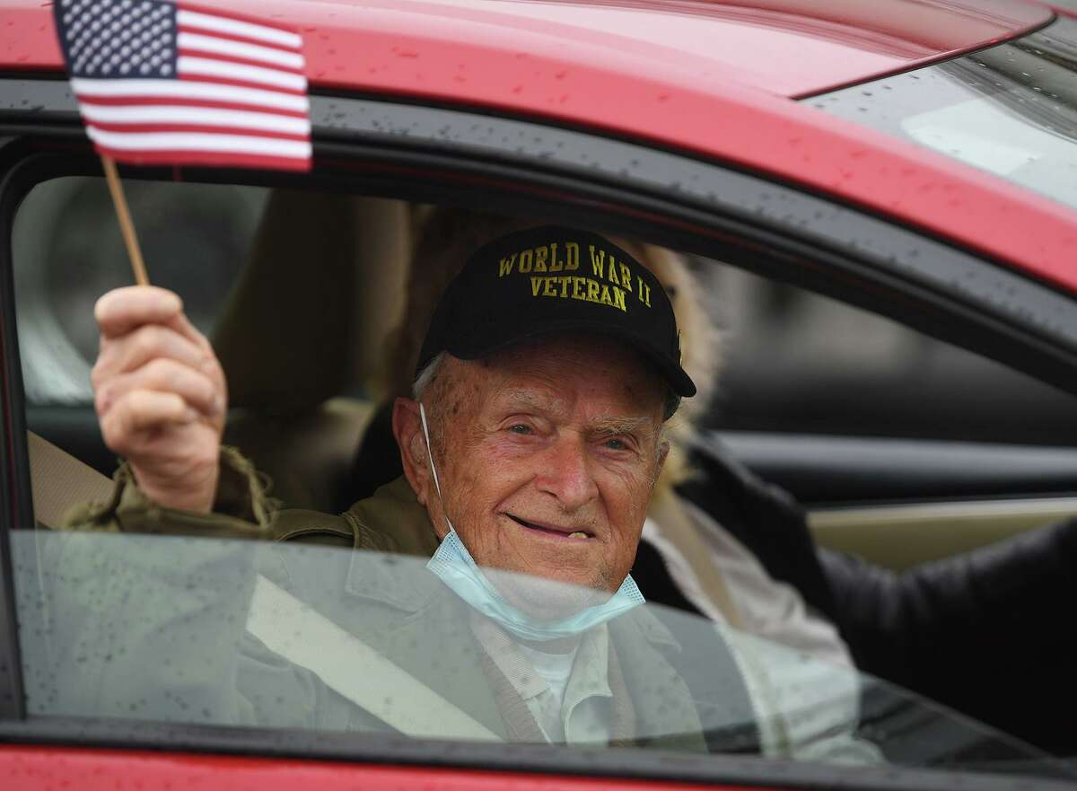 World War 2 veteran Matthew Pekata, 95, waves the flag as he is driven up to receive a Veterans Day takeaway breakfast at the Balwin Community Center Stratford, Conn. on Wednesday, November 11, 2020. Andreanos Wheway, a Stratford police officer for the past two years currently in the National Guard, waved to the veterans while standing in front of a cruiser bedecked with patriotic bunting for the occasion. He said he was happy to