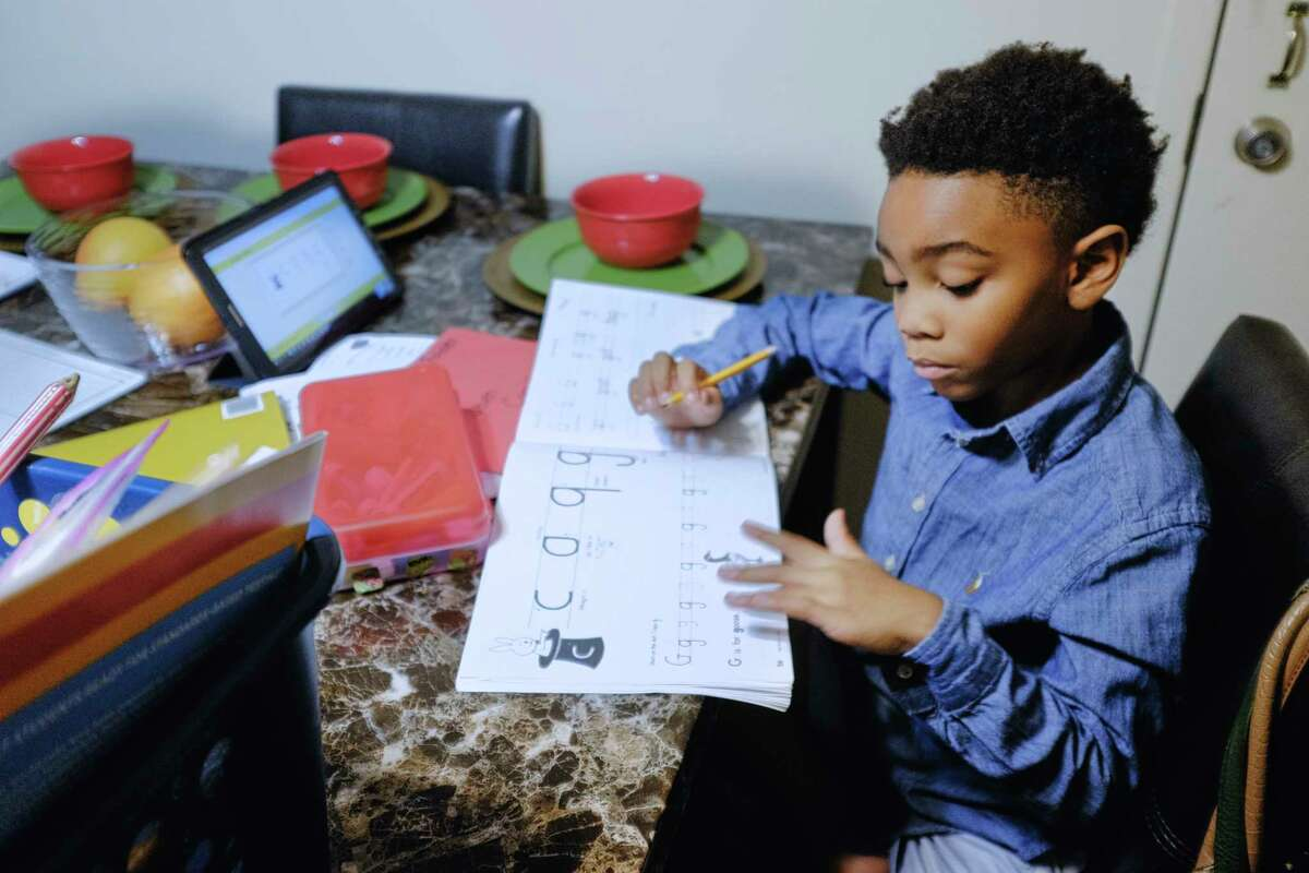 Jeven Cargill works on writing letters during his virtual school day on Tuesday, Oct. 27, 2020, in Albany, N.Y. (Paul Buckowski/Times Union)