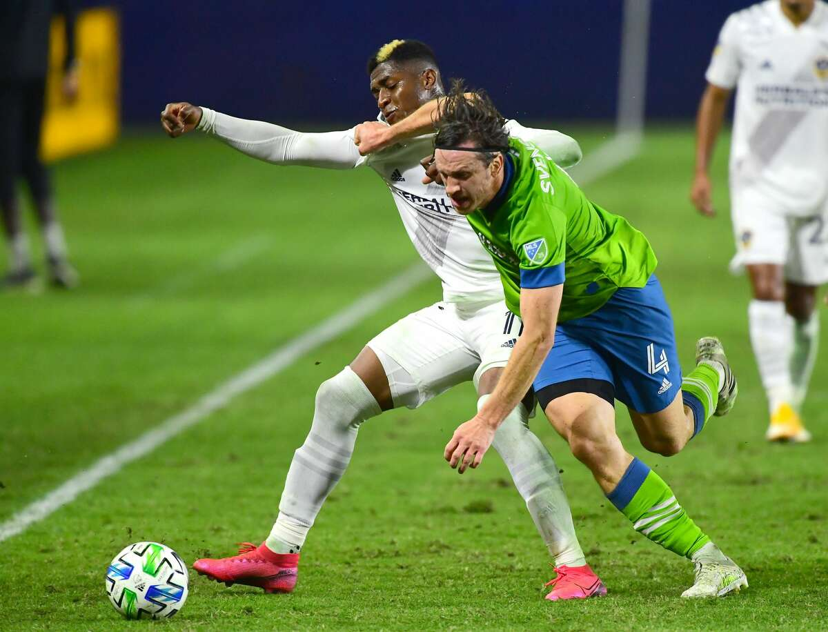 CARSON, CA - NOVEMBER 04: Gustav Svensson #4 of the Seattle Sounders and Yony Gonzalez #11 of the Los Angeles Galaxy battle for the ball in the first half of the game at Dignity Health Sports Park on November 4, 2020 in Carson, California. (Photo by Jayne Kamin-Oncea/Getty Images)