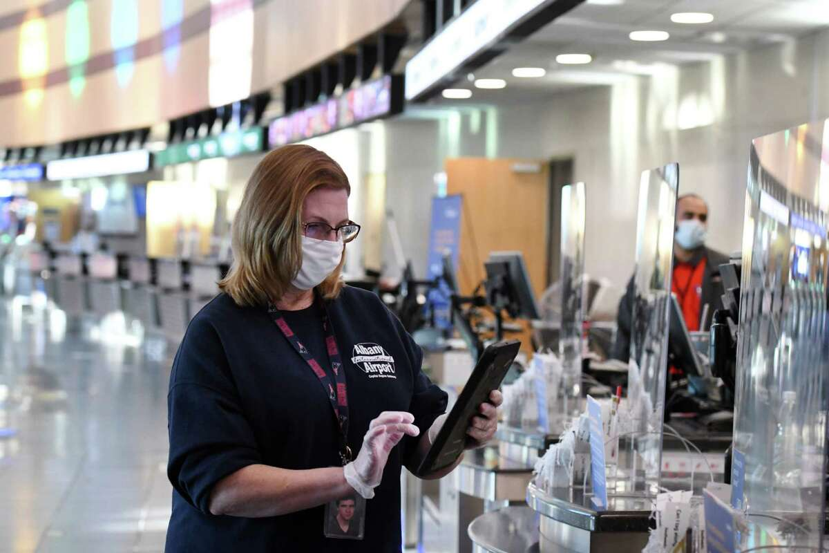 Airport custodian Magdalene Dennick enters information into a database app from GE Aviation after disinfecting a Southwest Airlines ticket counter at Albany International Airport on Tuesday, Nov. 10, 2020, in Colonie, N.Y. GE Aviation is introducing new technology at Albany International Airport that allows passengers to monitor disinfection schedules. (Will Waldron/Times Union)