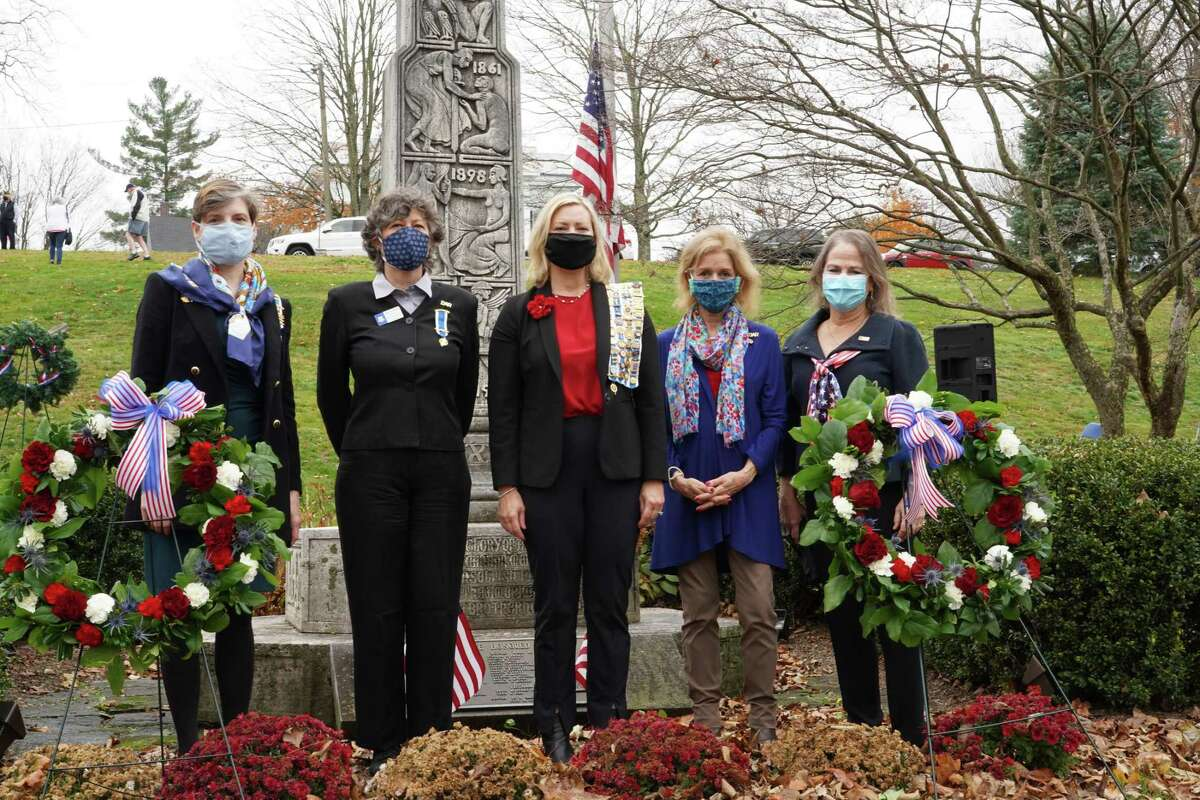 """Members of the Hannah Benedict Carter Chapter of the Daughters of the American Revolution stood in front of the wreaths that were placed during the New Canaan Veterans Day ceremony, on Nov. 11, 2020 at God's Acre. From Left to right, Sarah Coleman, Rose Scott Rothbart, Lisa Melland, Susan Kniffen and Ellen Taylor Sisson. New Canaan's most """"illustrious"""" Revolutionary War Veteran will be part of America's 250, a commission set up to celebrate America's 250th year in 2026. Betts """"had done so much to aide in the cause of American freedom,"""" Melland said. """"On his own account he fought in 13 revolutionary battles,"""" and she has found evidence that he was at Valley Forge and at Yorktown. He received """"a commendation from George Washington for his valiant efforts at the Battle of Norwalk,"""" Melland said. The local DAR also learned that Betts had a slave called Jessie Betts, who is buried near him in St. Mark's Cemetery, located at the corner and Weed Street and Sunset Hill Road. """"We have now included full researched information about Jessie Betts in the video,"""" she said. """"Over the next years our chapter will do a deep research dive to determine other enslaved individuals, and patriots of color who are buried here in New Canaan,"""" Melland said."""