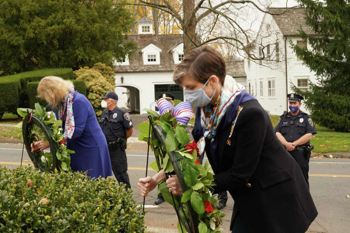 """Members of the Benedict Carter Chapter of the Daughters of the American Revolutions set up the wreaths during the Veterans Day ceremony in God's Acre in New Canaan on Nov. 11, 2020. The national Society of the Daughters of the American Revolution DAR """"established the Forgotten Patriots in the 1980's, to focus on the important contributions made by African American, indigenous peoples and individuals of mixed heritage who supported the American revolution,"""" Melland said. Moynihan introduced the main speaker for the ceremony, Tyler Nash of Darien, and shared his biography. Nash is a former U.S. Army Infantry Officer, who has been awarded commendations for both Joint Service and service in the Army, as well as across two separate Afghanistan Campaigns. He completed his service at the rank of captain. Nash entered military service after receiving a full Army ROTC scholarship to Fordham University in 2008 and was recognized as Fordham's Distinguished Military Graduate in 2012. He was assigned to the 10th Mountain Division and deployed to Eastern Afghanistan, where he became platoon leader. Nash was selected for a special operations assignment to the 75th Ranger Regiment. His final assignment was to the 1st Armored Division's where he represented an installation of over 33,000 as a participant in the 2018 David E. Grange, Jr. Best Ranger Competition."""