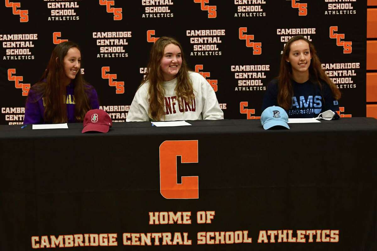 Cambridge athletes (sitting from left) Lilly Phillips (UAlbany basketball), Fiona Mooney (Stanford rowing), and Sophie Phillips (Rhode Island basketball), briefly take their masks off for photos after signing letters of intent at Cambridge High School on Wednesday, Nov. 11, 2020 in Cambridge, N.Y. (Lori Van Buren/Times Union)