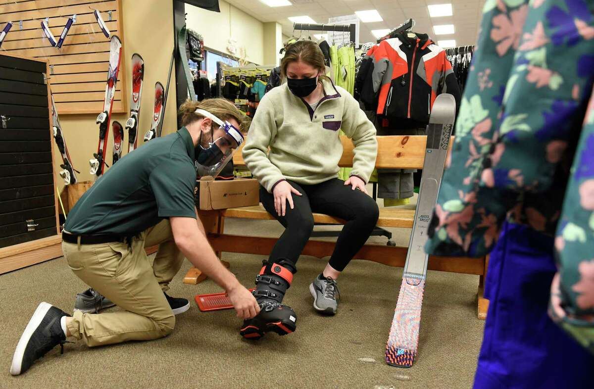Employee Alex McDaniel helps Colleen Heck try on a pair of K2 ski boots at Alpin Haus on Wednesday, Nov. 11, 2020 in Clifton Park, N.Y. Alpin Haus CEO Bud Heck was named the 2021 Civitella Entrepreneur of the Year by Siena College. (Lori Van Buren/Times Union)