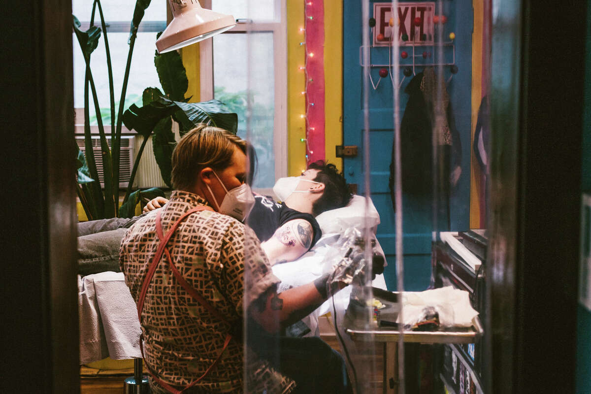 Jess Koala tattoos a custom design on her partner (and client for the day), Noelle Rupp, at Castro Tattoo.