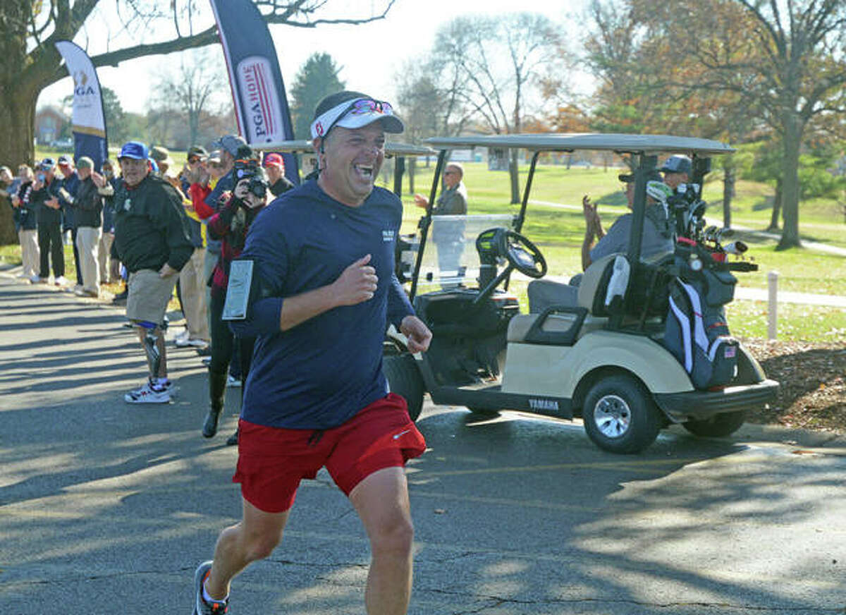 Mike Suhre, vice president and head PGA golf professional at Oak Brook Golf Club, prepares to cross the finish line Wednesday after running 10 miles from Oak Brook to Sunset Hills Country Club as part of a fundraiser for PGA HOPE.