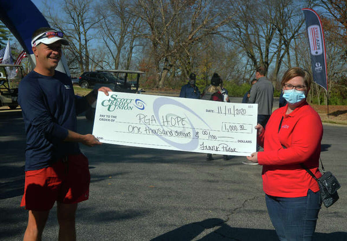 Mike Suhre, left, vice president and head PGA golf professional at Oak Brook Golf Club, receives a check to PGA HOPE from Kelsey Thomas, community relations representative from Scott Credit Union on Wednesday at Sunset Hills Country Club. Suhre ran 10 miles from Oak Brook to Sunset Hills to raise money for the charity.