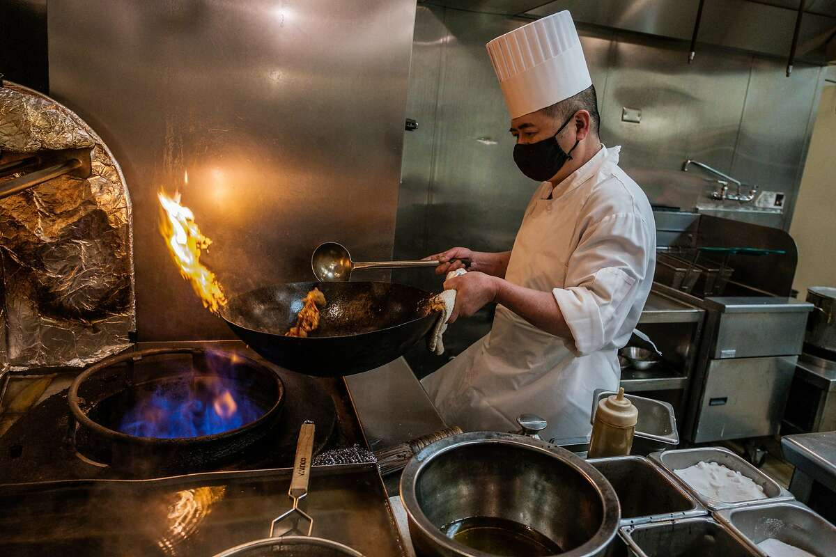 Chef Chao Hua Lei prepares a dish in a wok on a gas stove at Yank Sing. The S.F. supervisors' move to ban natural gas use in new buildings provides for a waiver for restaurant spaces.
