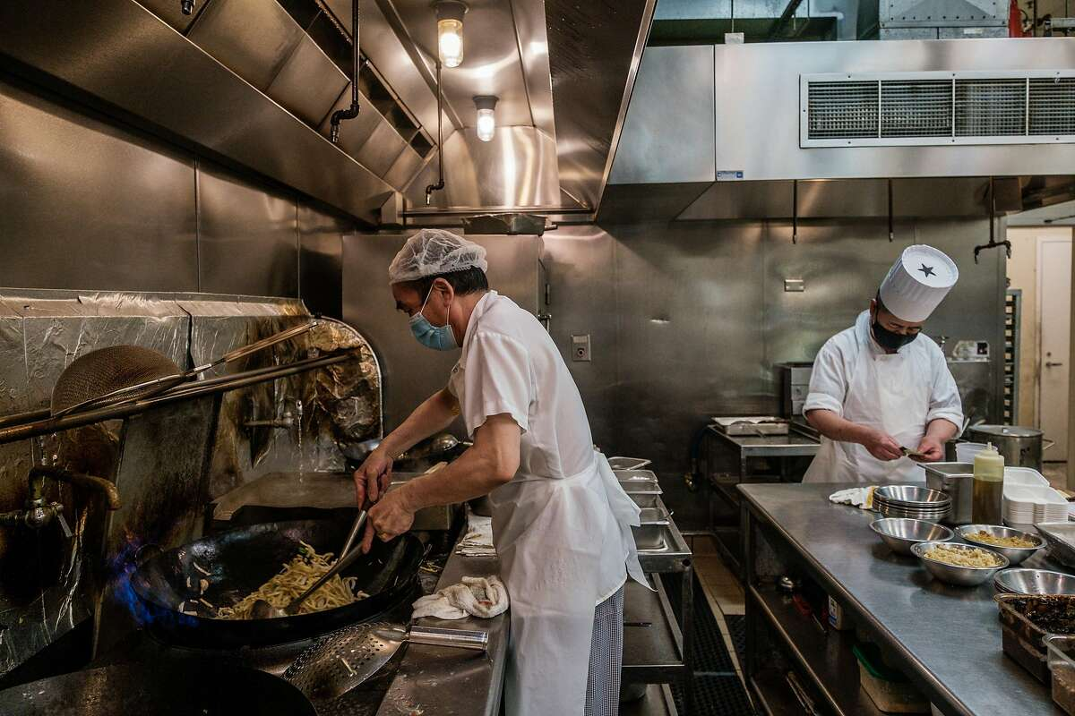 Line cook Jing Zhen Hu (left) and Chef Chao Hua Lei prepare dishes at Yank Sing. Entertainment Commissioner Steven Lee, who is an investor in the historic Sam Wo Chinatown restaurant, said thinks restaurants should be exempt from the natural gas ban, saying,