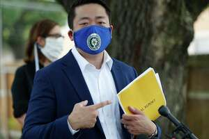 State Rep. Gene Wu, D-Houston, points to his copy of an audit of the Houston Police Department's narcotics division as he speaks to the media Thursday, July 2, 2020, in Houston, in front of the home where Rhogena Nicholas and Dennis Tuttle were killed on Harding Street.