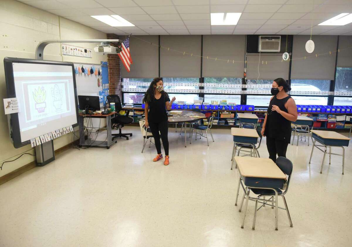 Teachers Maria Florian, left, and Lee-Ann Baranowski chat while setting up their classrooms at Springdale Elementary School in Stamford, Conn. Tuesday, Sept. 1, 2020.