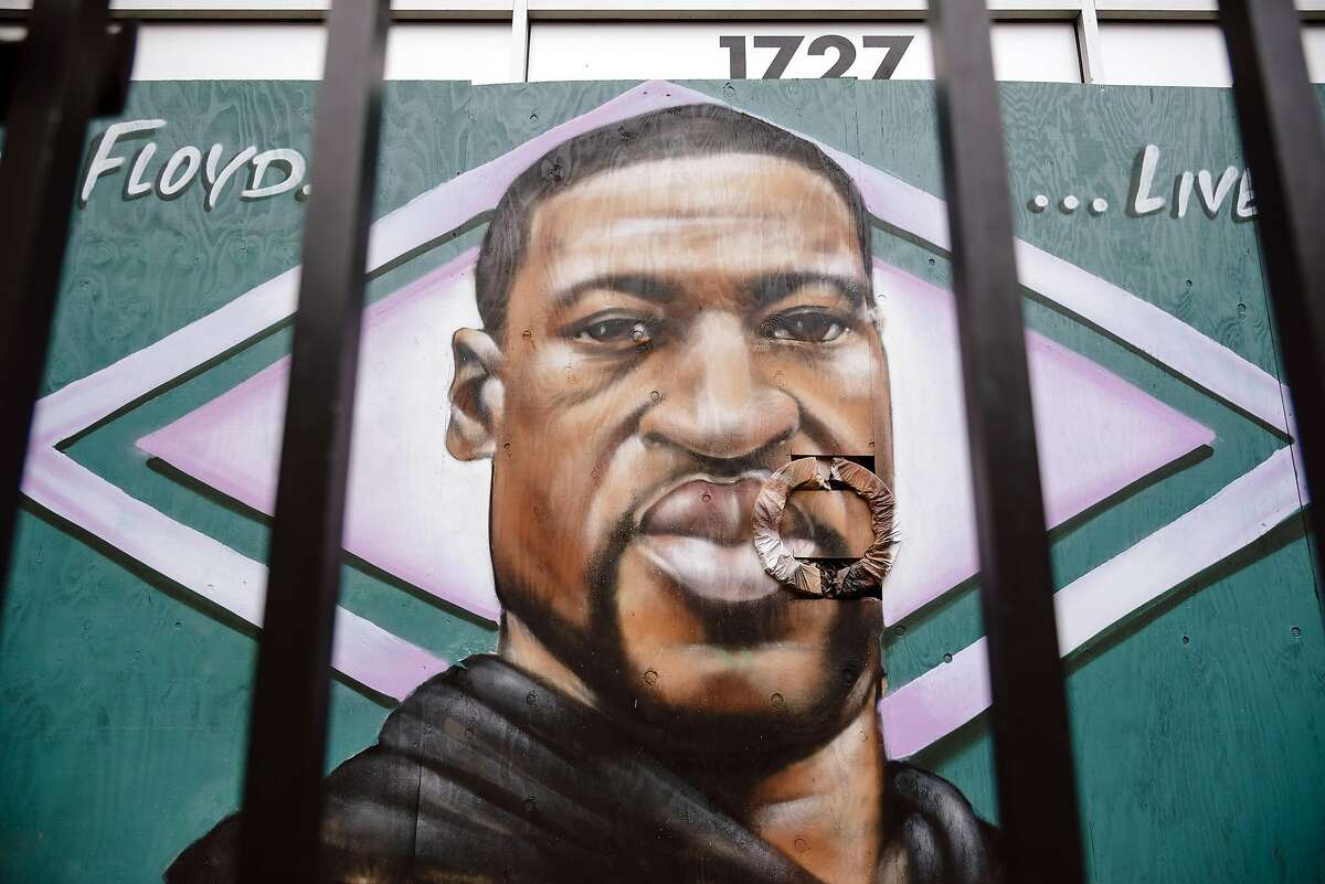A mural honoring George Floyd is painted on the facade of the boarded up SomŠr Bar and Lounge in Oakland, Calif, on Sunday, May 31, 2020.