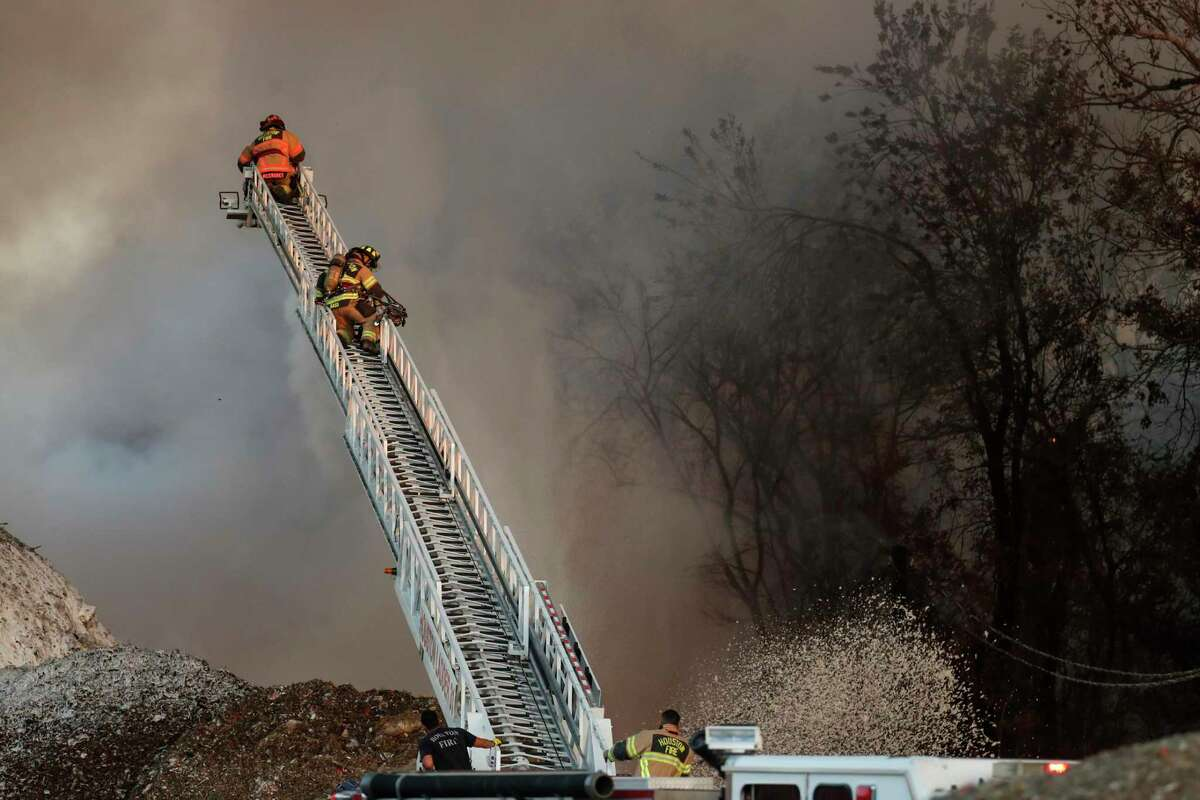 Firefighters battle a trash fire at a recycling facility near the corner of Irvington and Bennington on Wednesday, Nov. 11, 2020 in Houston.