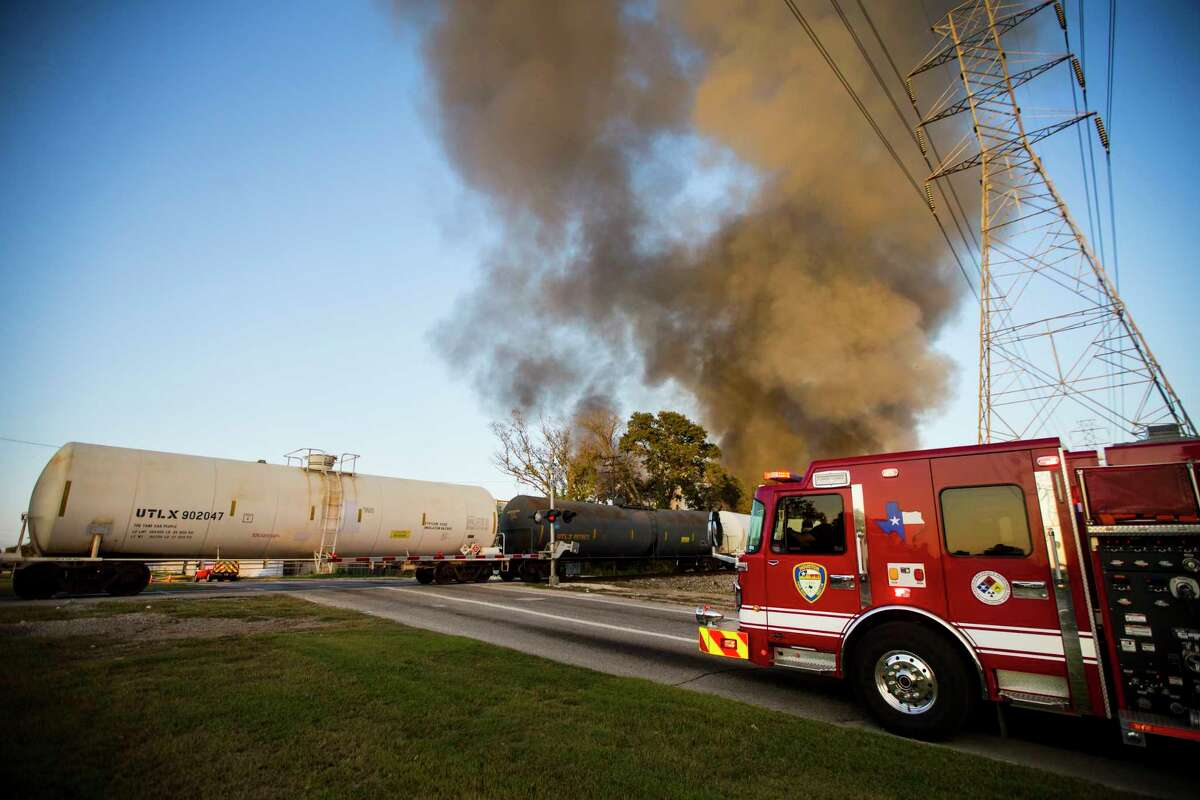 A fire truck is forced to wait for a train to pass before it can cross over to get in position to battle a trash fire at a recycling facility near the corner of Irvington and Bennington on Wednesday, Nov. 11, 2020 in Houston.