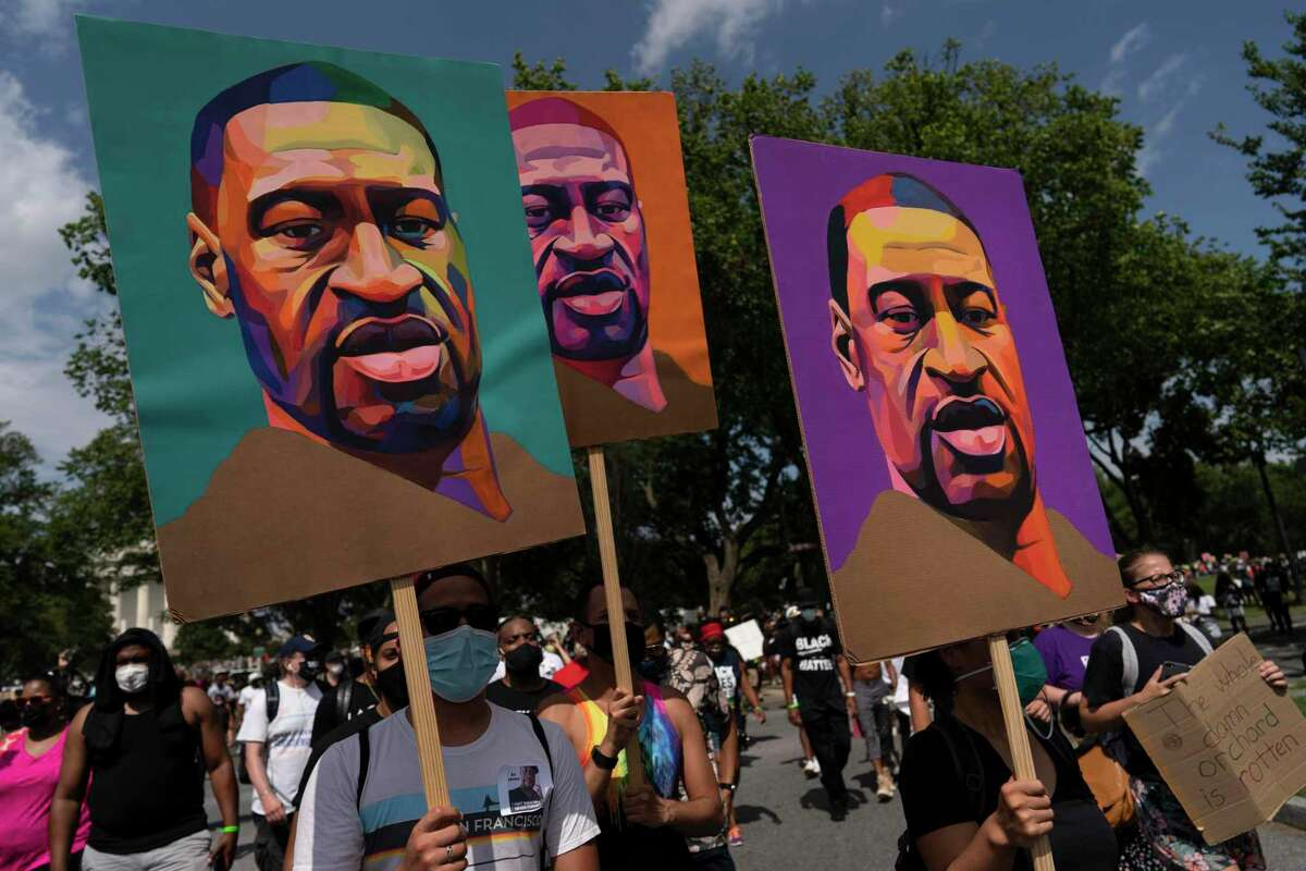 People carry posters of George Floyd as they march from the Lincoln Memorial to the Martin Luther King Jr. Memorial during the March on Washington, Friday Aug. 28, 2020, in Washington. (AP Photo/Carolyn Kaster)