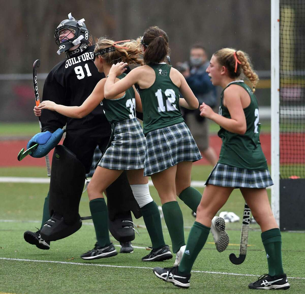 Guilford goalkeeper Eve Young, left, celebrates with teammates after its 5-1 win over Cheshire in the SCC Division A field hockey championship at Cheshire High on Wednesday.