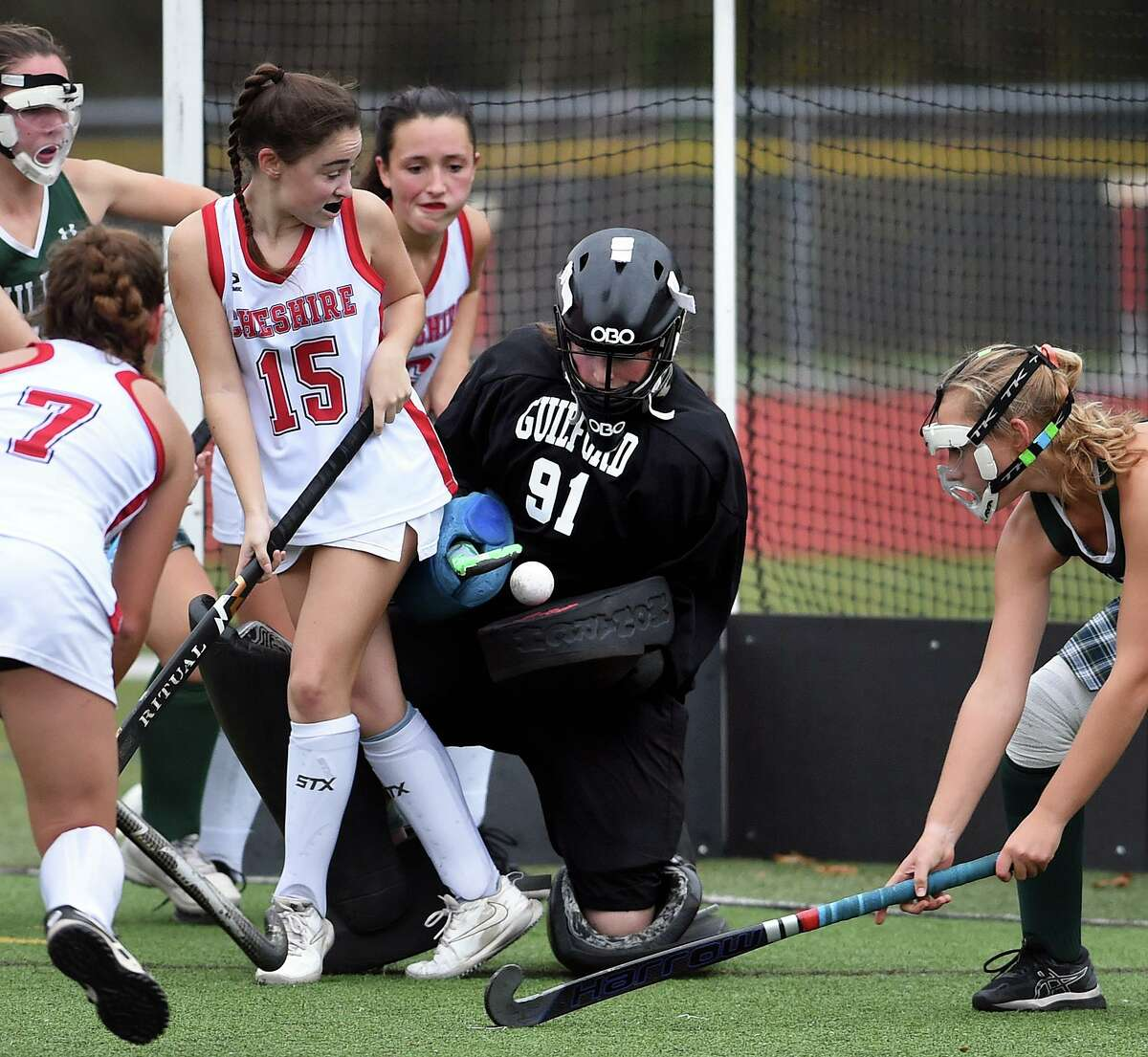 Guilford goalkeeper Eve Young (center) blocks a shot from Cheshire in the fourth quarter of the SCC Division A field hockey championship at Cheshire High School on November 11, 2020.