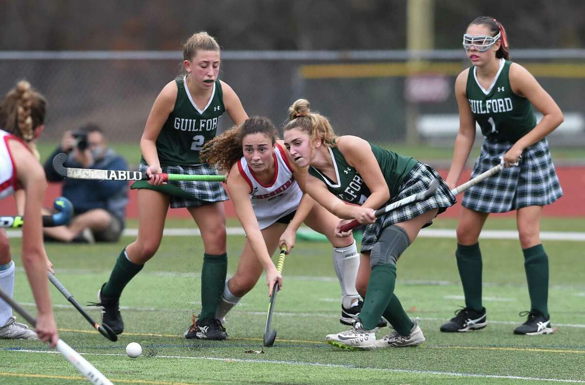 Cheshire's Sophia Vagts, center left, and Guilford's Ella Kagan, center right, fight for the ball in the SCC Division A field hockey championship at Cheshire High last month.