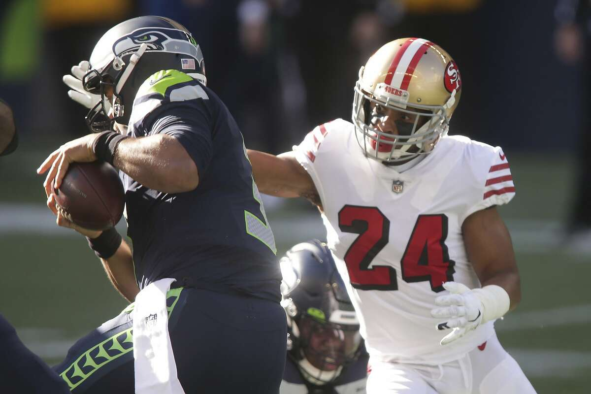 San Francisco 49ers' K'Waun Williams pressures Seattle Seahawks quarterback Russell Wilson, left, during the first half of an NFL football game, Sunday, Nov. 1, 2020, in Seattle. (AP Photo/Scott Eklund)
