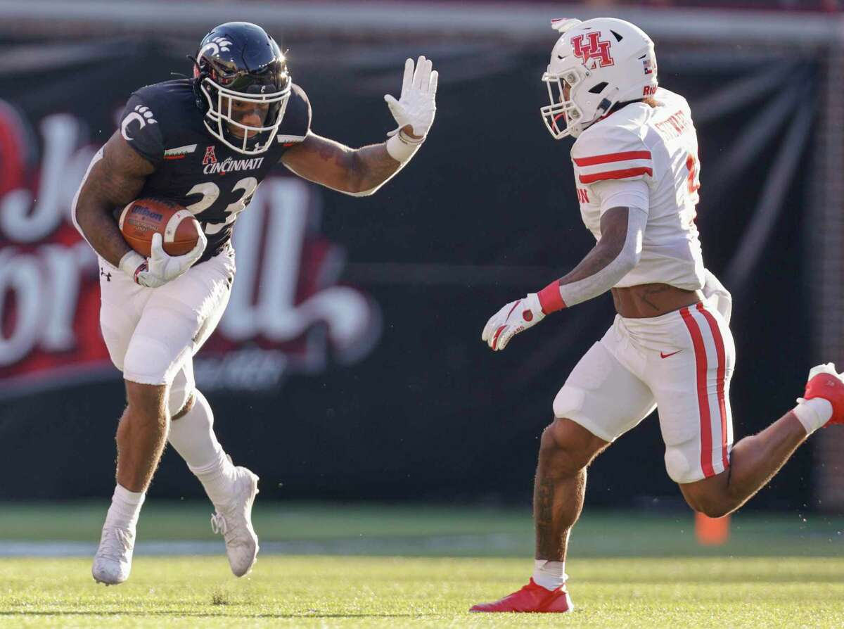 Gerrid Doaks, left, and Cincinnati did a good job of keeping JoVanni Stewart and the rest of UH's defense at a distance last Saturday, amassing 342 rushing yards in a 38-10 victory over the Cougars.