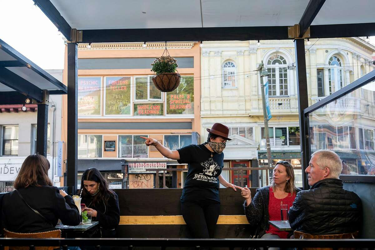 People sit in the parklet along Columbus Avenue at Devil's Acre bar in North Beach in S.F., which did not yet go into the purple tier.