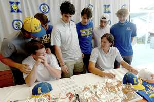 Monsignor Kelly Catholic basbeall players congratulate teammates UT-Austin bound Gavin Kash (right) and future Navarro College player Pierce Leventhal after they signed their commitment letters at 5 Under Golf Wednesday. Photo taken Wednesday, November 11, 2020 Kim Brent/The Enterprise
