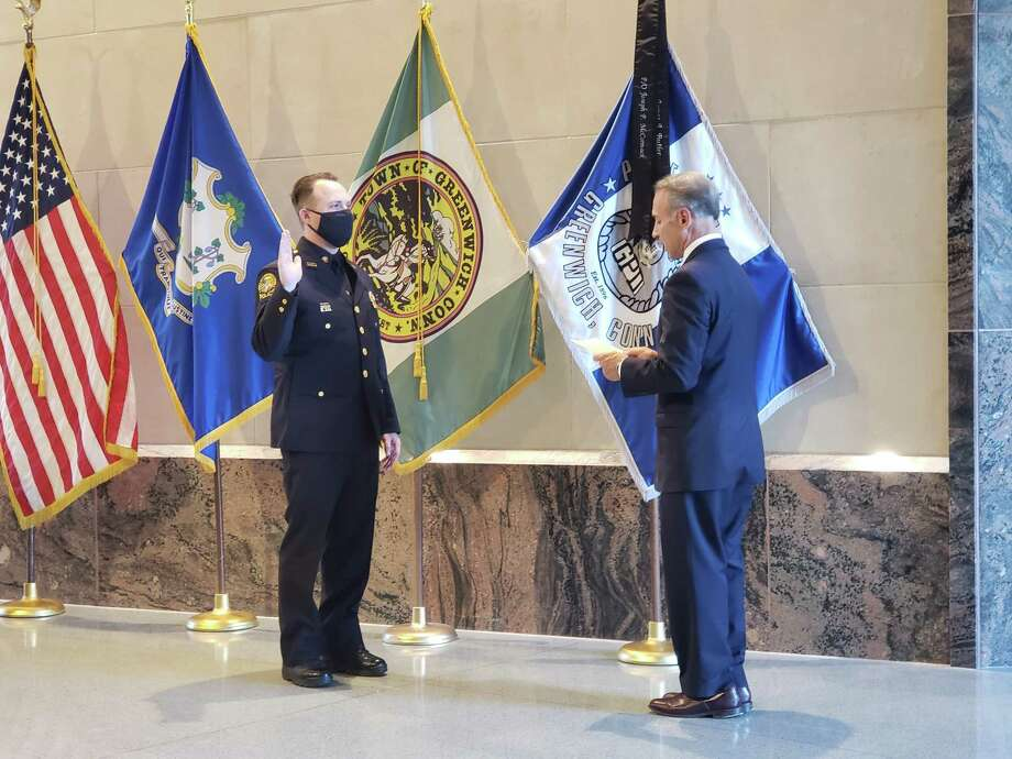 Sgt. Daniel Bucci is given the oath of office by First Selectman Fred Camillo. Photo: Contributed / Greenwich Police Department
