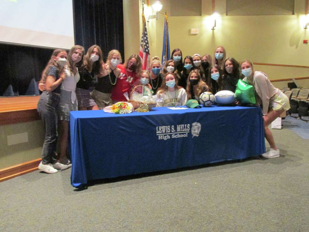 Lewis Mills teammates and friends gather around Abby Mills at her DI signing with William and Mary College Wednesday morning at Lewis Mills High School.